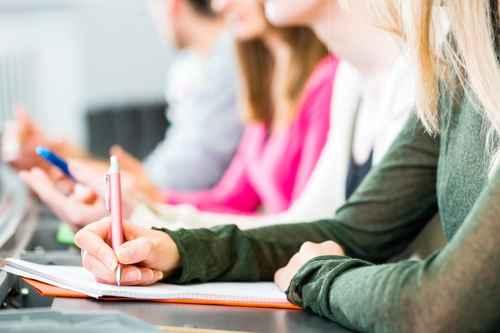 Studenten im Uni Hörsaal schreiben Klausur